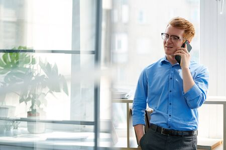 Young restful office worker consulting someone on smartphone Stock Photo