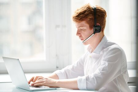 Young operator of call center communicating with online clients Banco de Imagens
