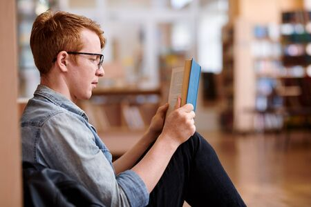 Young reader in casualwear reading by bookshelf in library Stok Fotoğraf