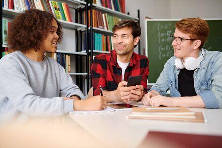 Groupe d'adolescents assis par table dans la bibliothèque du collège tout en discutant de nouvelles idées Banque d'images