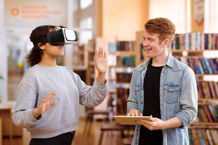 Happy student with tablet interacting with his classmate with vr headset