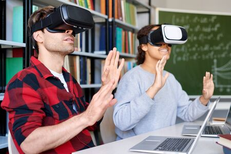 Two amazed classmates in vr goggles touching virtual stuff