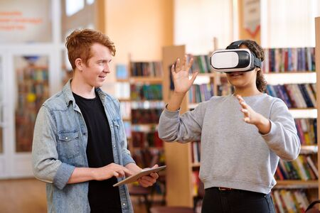 Mixed-race student with vr headset and her classmate with touchpad