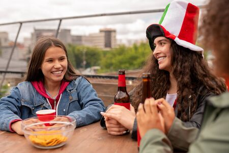 Cheerful pretty girls with drinks talking by table after football match