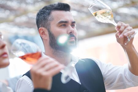 Young confident sommelier with glass of cabernet sauvignon Standard-Bild - 127380797