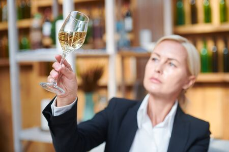 Female hand holding bokal woth white wine while examining its color Standard-Bild - 127380931