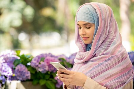 Young Arabian woman wearing hijab scrolling in her smartphone