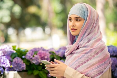 Pretty young muslim woman in hijab scrolling in smartphone outdoors Imagens