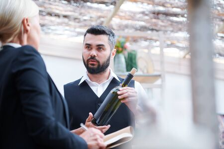 Young confident cavist with bottle of wine talking to his colleague Standard-Bild - 127381184
