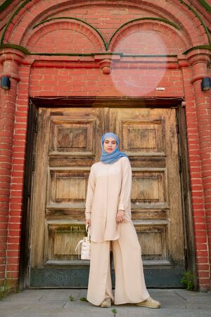Young muslim woman in blue hijab and beige casualwear Banque d'images - 127381188