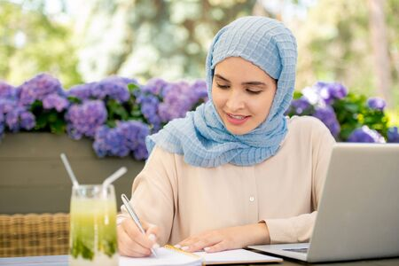 Pretty muslim student in hijab making notes in notebook outdoors