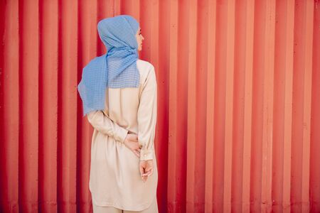 Back view of young muslim female in blue hijab and light beige casualwear