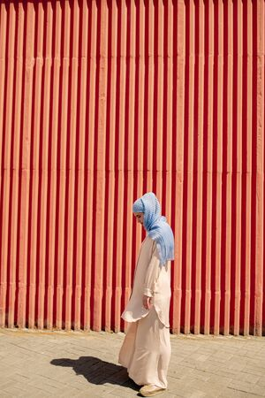 Young muslim female in casualwear and hijab standing by red wall