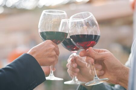 Hands of friends or business partners clinking with wineglasses with red wine while celebrating successful deal or other event