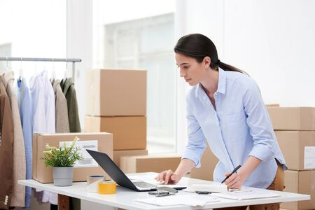 Young woman in casualwear looking at laptop display while making notes