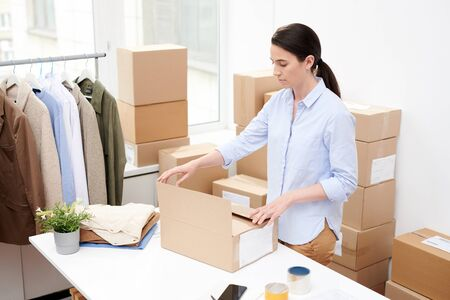 Young office manager in casualwear packing order for client