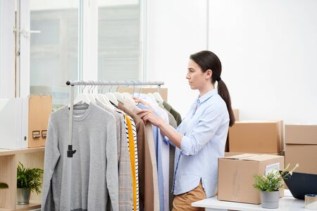 Manager of contemporary online casualwear shop choosing clothes for clients Stock Photo