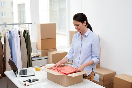 Young attractive woman in casualwear putting folded red pullover into box