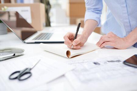 Female manager of online shop making notes on blank page of notebook Reklamní fotografie