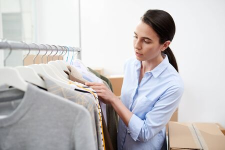Young designer of clothes looking through new collection of casualwear in studio Stock Photo
