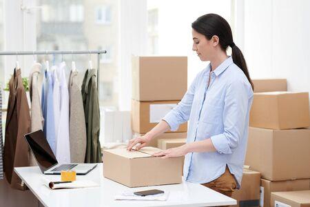 Giovane manager della scatola di imballaggio del negozio online con abbigliamento casual