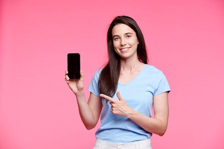 Young smiling woman pointing at touchscreen of smartphone Foto de archivo - 129737942