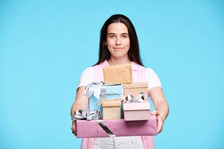 Young brunette female giving you stack of giftboxes Stock Photo