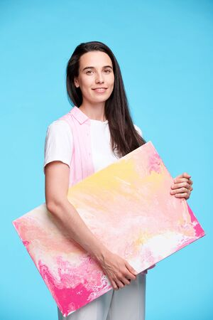 Happy young brunette woman holding artwork Stockfoto