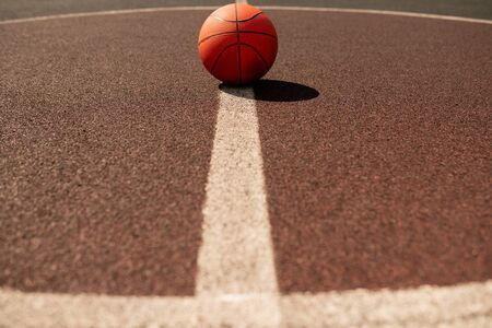 Ball for playing basketball lying in the center of vertical white line