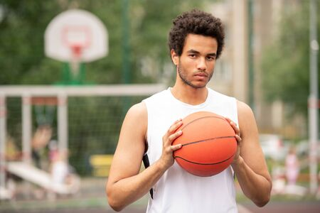 Young serious multicultural athlete holding ball for playing basketball