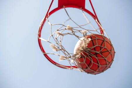 Ball in basketball net with light blue cloudless sky on background