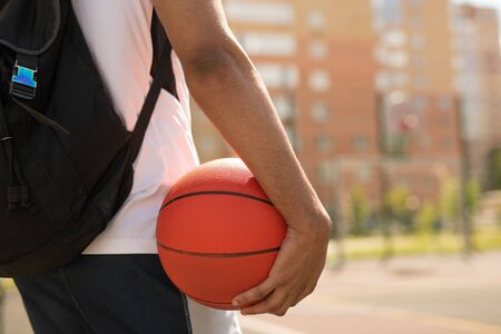 Young basketball player with ball and backpack