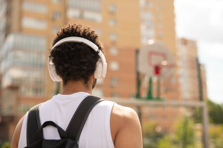 Rear view of young intercultural sportsman with headphones and backpack
