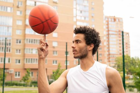 Young active professional basketball player holding rotating ball on forefinger