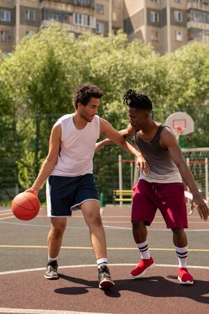 Two intercultural basketball playmates playing or training on the court
