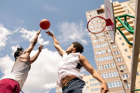 Below view of two intercultural rivals trying to catch ball in motion while training at outdoor court
