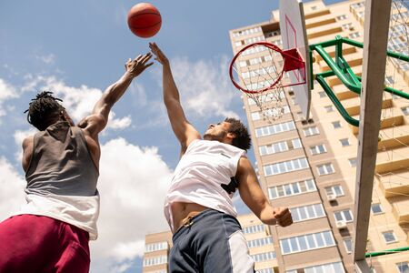 Young active players in sportswear jumping while trying to catch the ball during game of basketball outdoors