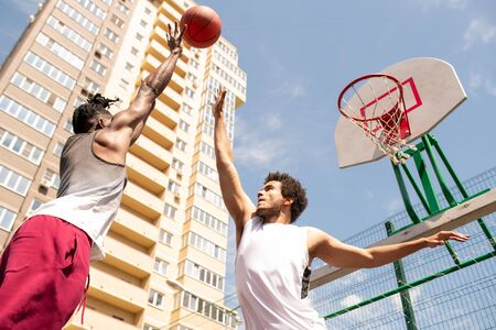 Two young professional intercultural basketball players trying to catch the ball Standard-Bild