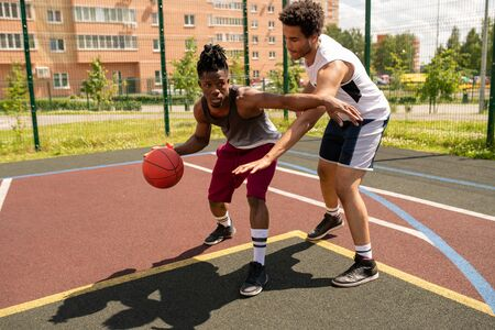 Young basketball instructor helping African sportsman with one of exercises