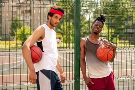 Two active guys in sportswear standing by fence surrounding basketball court Standard-Bild