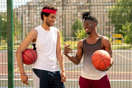 Two young friendly basketball playmates discussing some curious moments of game
