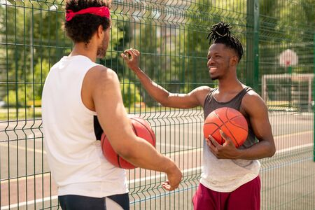 Two young multicultural basketball players interacting after game