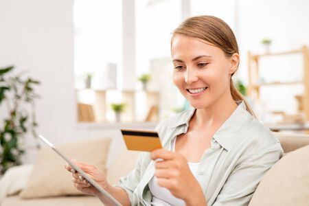 Young woman with tablet reading data on card while paying for online order Stock Photo