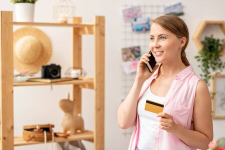 Casual young woman with smartphone and plastic card making order by phone