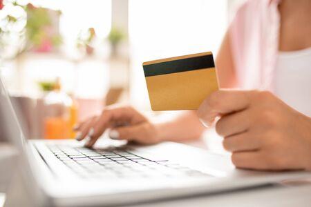 Compradora femenina contemporánea con tarjeta de plástico ingresando sus datos personales