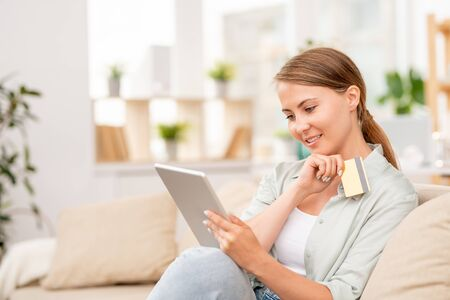 Pretty girl with touchpad and plastic card looking through goods in online shop