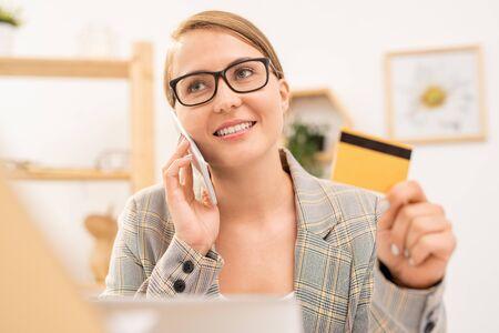 Happy elegant businesswoman in eyeglasses making order by phone