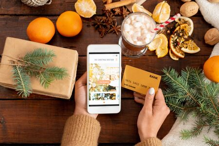 Overview of human hands with smartphone and credit card among xmas stuff Stock Photo