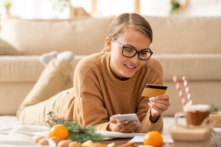 Young casual woman with smartphone and credit card looking at personal data Imagens