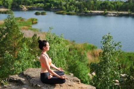 Young woman in sports clothing sitting in lotus position Stockfoto